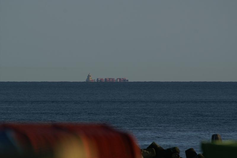 An einem am Horizont vorbeifahrenden Schiff kann von der Helgoländer Düne aus eine Luftspiegelung wahrgenommen werden.