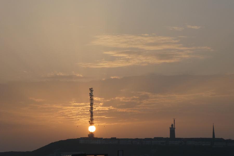 Die Sonne direkt hinter der Gitterkonstruktion des Telekommastes von der Düne aus gesehen.