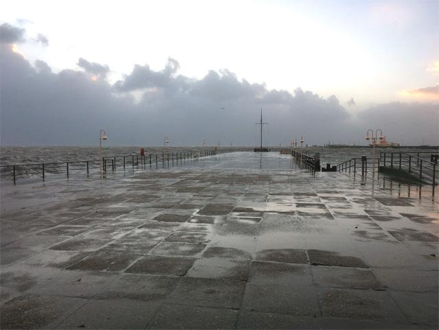Bei Sturm wird die Landungsbrücke  Helgolands von besonders hohen Wellen überspült – Sturmflut.