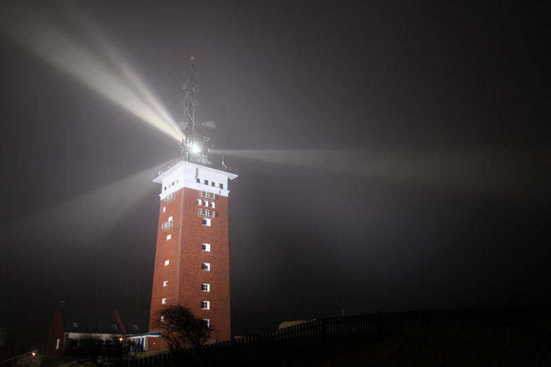 Helgolands Leuchtturm nachts in grellem Scheinwerferlicht.